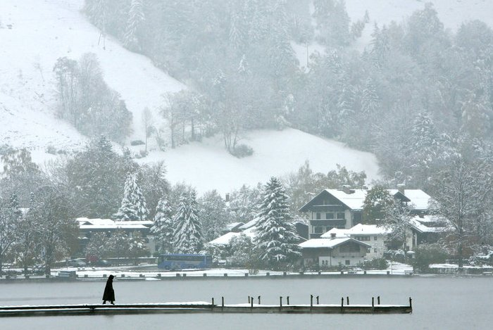 woman walks on a pier over lake Schliersee near Munich Germany