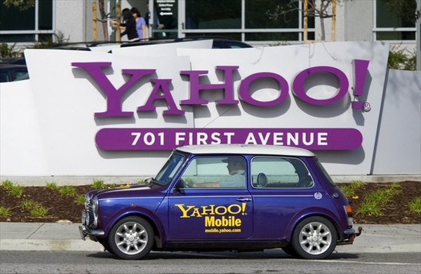 man drives a Mini Cooper with a Yahoo! logo in front of Yahoo! headquarters