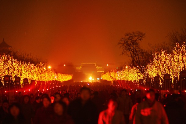 Visitors look at the laser performance in front of the Yongdingmen Gate