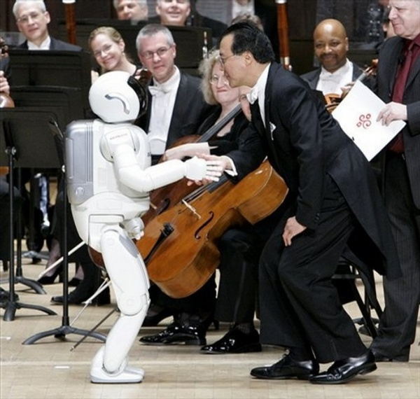 Cellist Yo-Yo Ma, right, greets Honda's ASIMO robot after it conducted the Detroit Symphony Orchestr