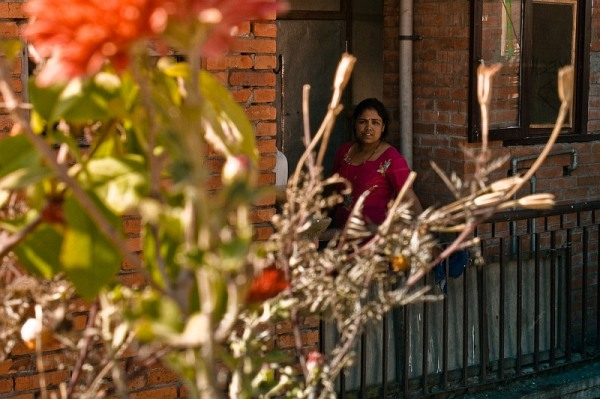 nepal_bhaktapur_woman_and_the_red_flower_on_a_roof_IMG_0266.jpg