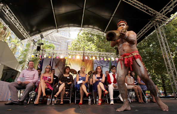 Newly announced Australian Citizens watch a greeting by an Aboriginal dancers